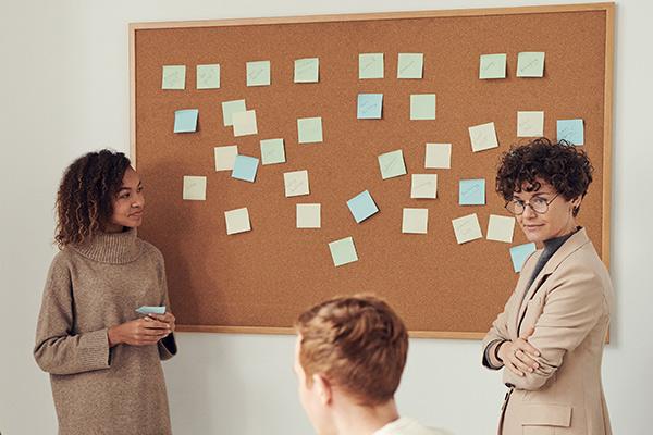 two women beside bulletin board