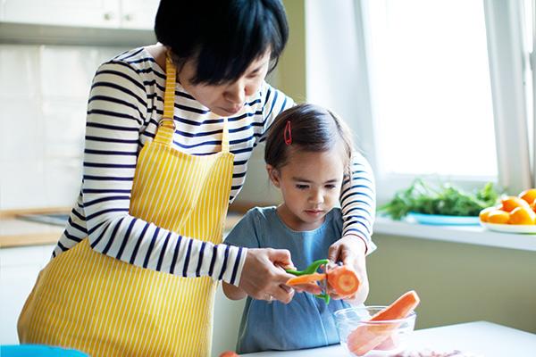 Mom and girl preparing food.
