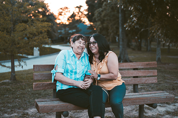 A woman sits with her older mother on a park bench.
