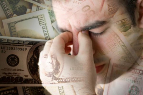 Person pinching top of nose to relieve stress from finances