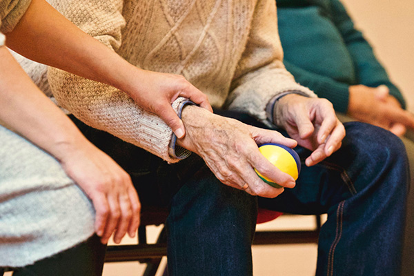 Older adults in a class sitting holding a tennis ball